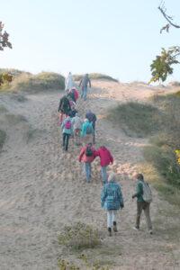 wandelaars beklimmen duin