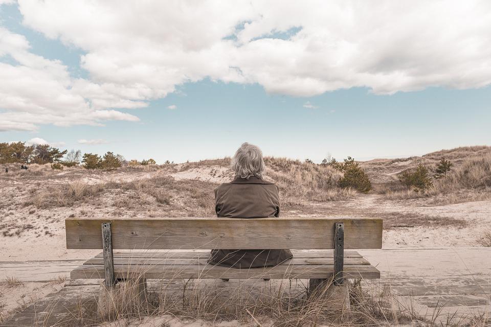 oudere vrouw op bankje in duinen