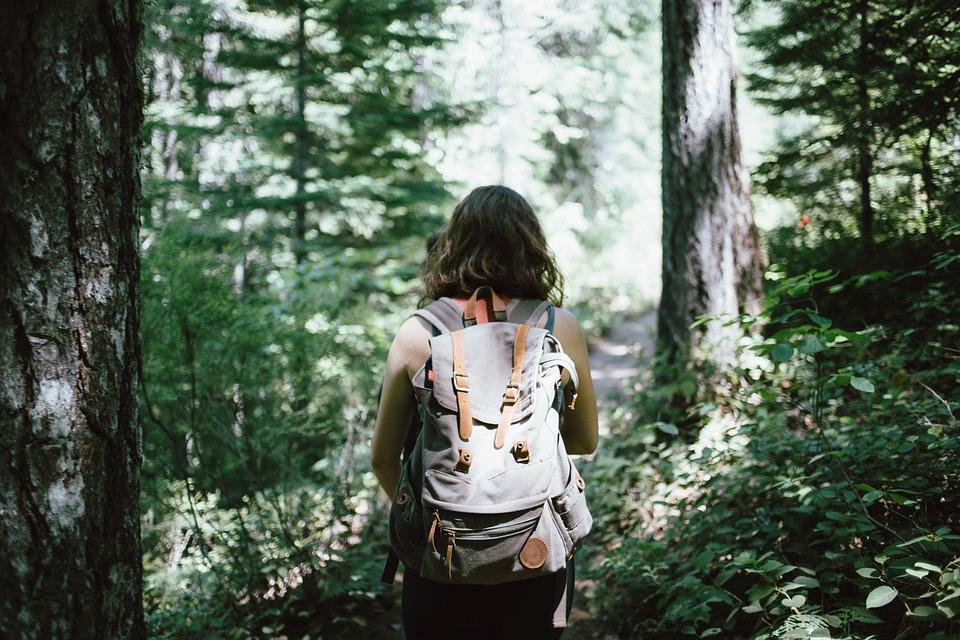 wandelende jonge vrouw in bos